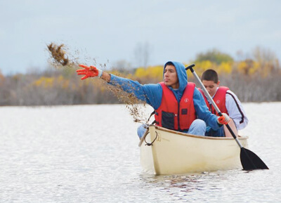 Two young men fishing in a canoe