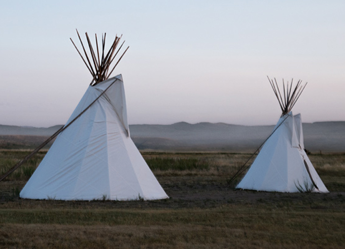 Sun setting on two tipis in the plains