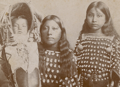 Two Native American girls and an infant in traditional dress