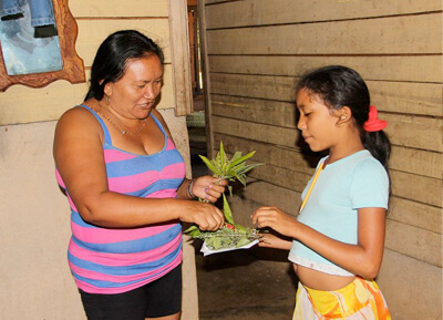 Native American mother and daughter tending to medicinal plants