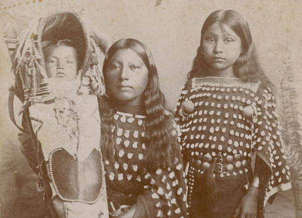 Two Kiowa girls and an infant in traditional dress