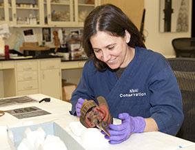 Lauren Anne Horelick examines a Tlingit ravens rattle