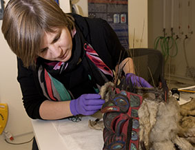 Sarah Owens examines a Tlingit frontlet headdress