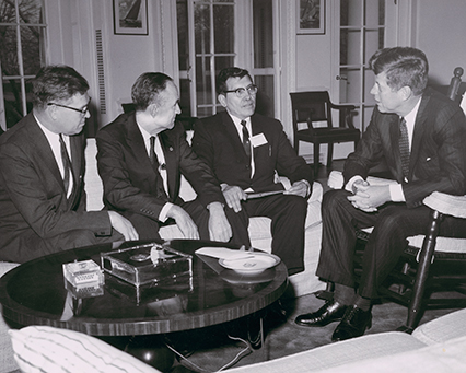 President John F. Kennedy meeting with National Congress of American Indians (NCAI) president Walter Wetzel, Senator Lee Metcalf, and Senator Mike Mansfield