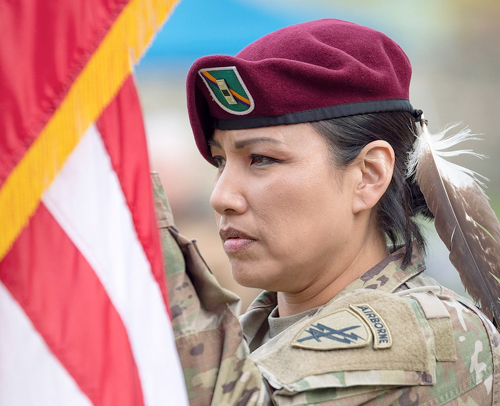 Native American woman veteran in military uniform holding the U.S. Flag