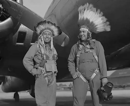 two native american military men in uniform standing in front of a military plane